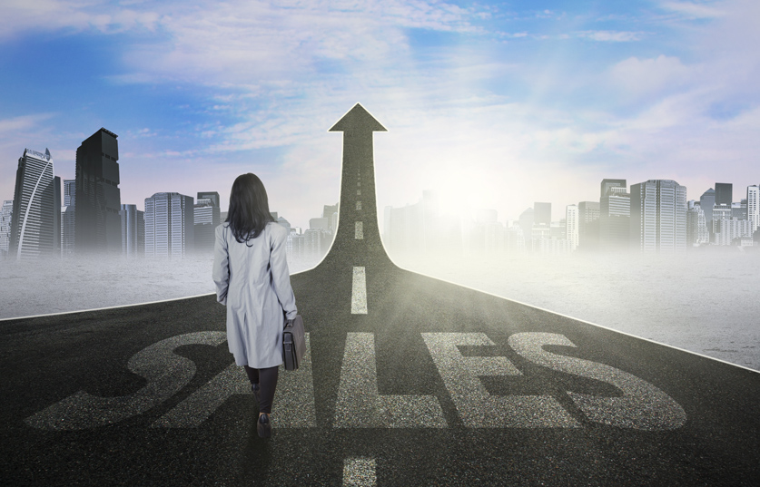 Image of businesswoman walking on the path with sales text and upward arrow